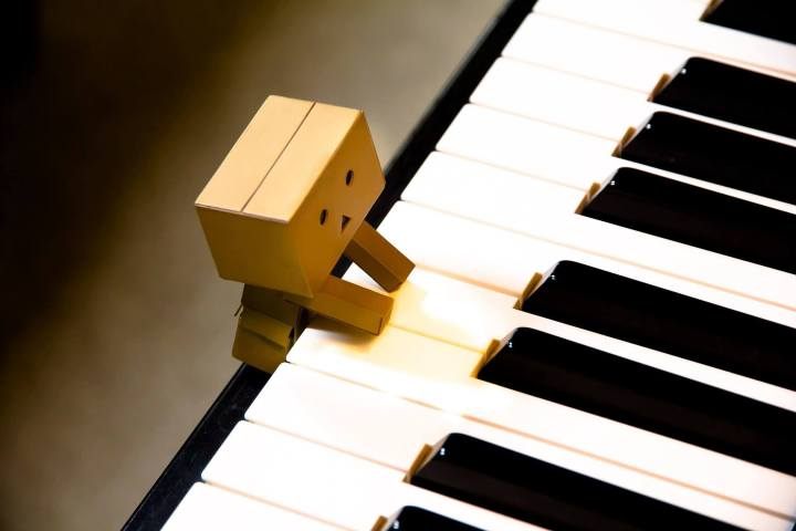 A tiny little cardboard box man plays a huge piano